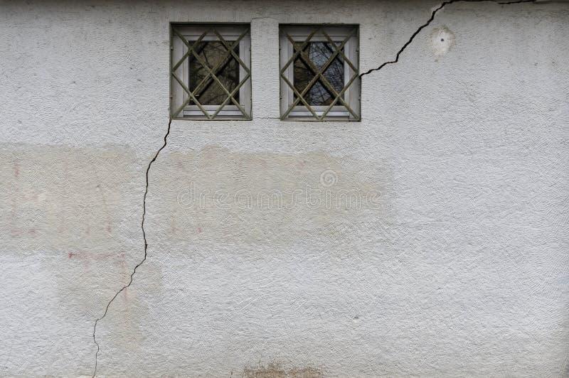 Facciata con 2 piccoli, le finestre escluse attraverso cui una crepa lunga ed ampia di circa 3 metri nella muratura funziona fotografie stock