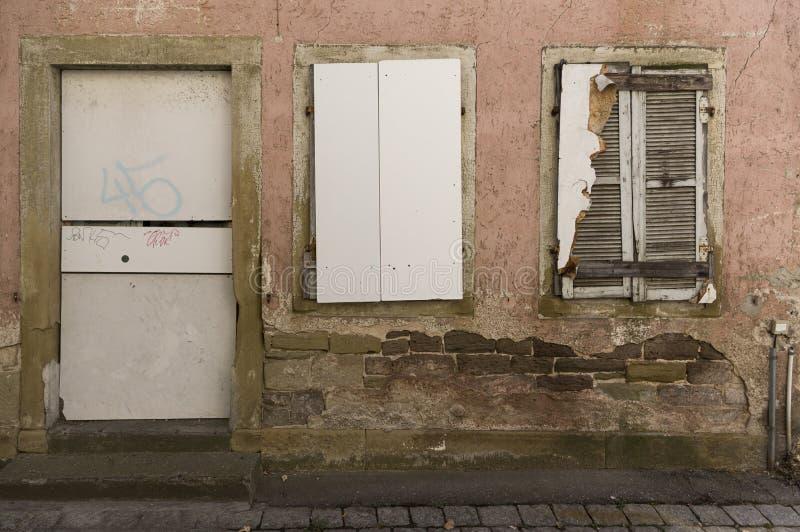 Facciata della casa abbandonata, imbarcata-su, dilapidata con la porta e di 2 finestre con gli otturatori immagine stock libera da diritti