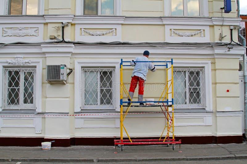 Facciata della pittura del lavoratore del costruttore di costruzione con il rullo fotografia stock libera da diritti