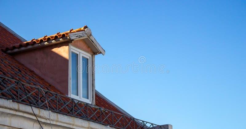 Facciata della soffitta con il tetto rosso sul fondo del cielo blu Piano superiore di costruzione antica Particolari di architett immagini stock