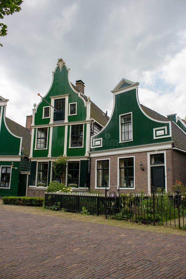 Facciata delle costruzioni olandesi tradizionali in villaggio Vecchio mattone e case di legno in Zaanse Schans, Paesi Bassi fotografie stock