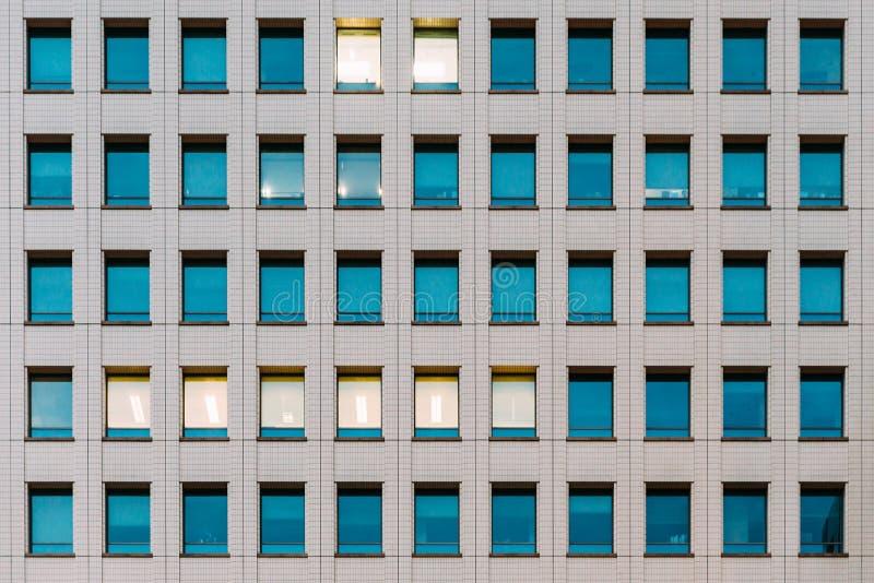 Facciata di costruzione moderna con colore del cielo di vetro di finestra riflesso ed alcune accese dall'interno immagini stock