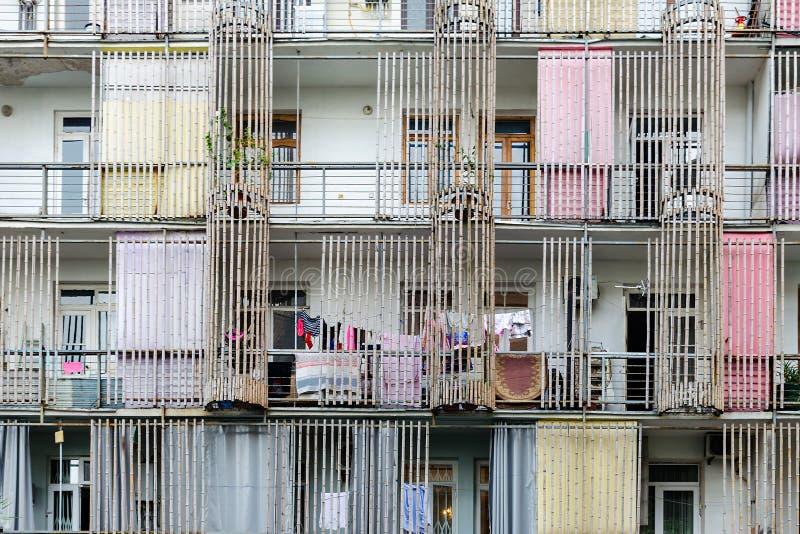 Facciata di un condominio, decorata con i tronchi di bambù, casa popolare accessibile, vestiti di secchezza che appendono su una  fotografie stock