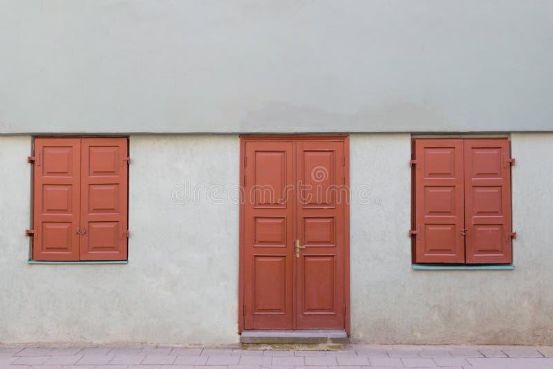 Facciata di vecchia casa con la porta di legno e due finestre chiuse fotografia stock