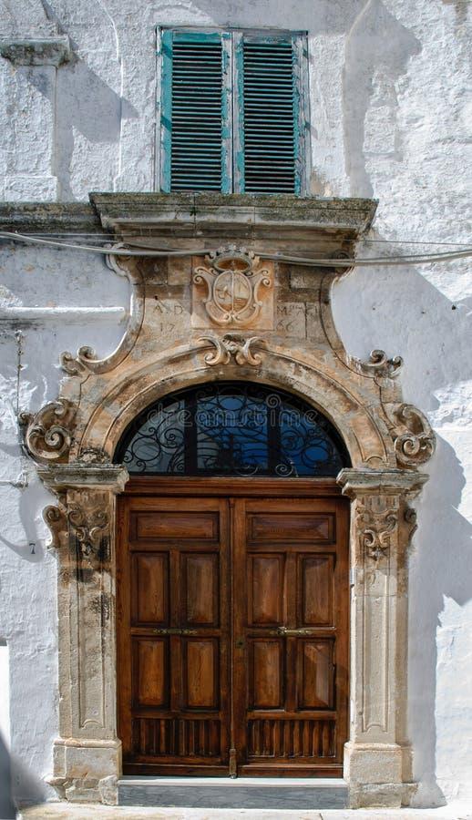 Facciata di vecchia costruzione con la porta magnifica nella vecchia città di Ostuni, La Citta Bianca immagini stock libere da diritti