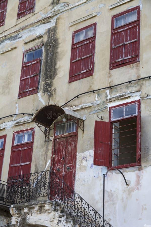 Facciata di vecchia costruzione con le porte e le finestre di legno rosse fotografia stock libera da diritti