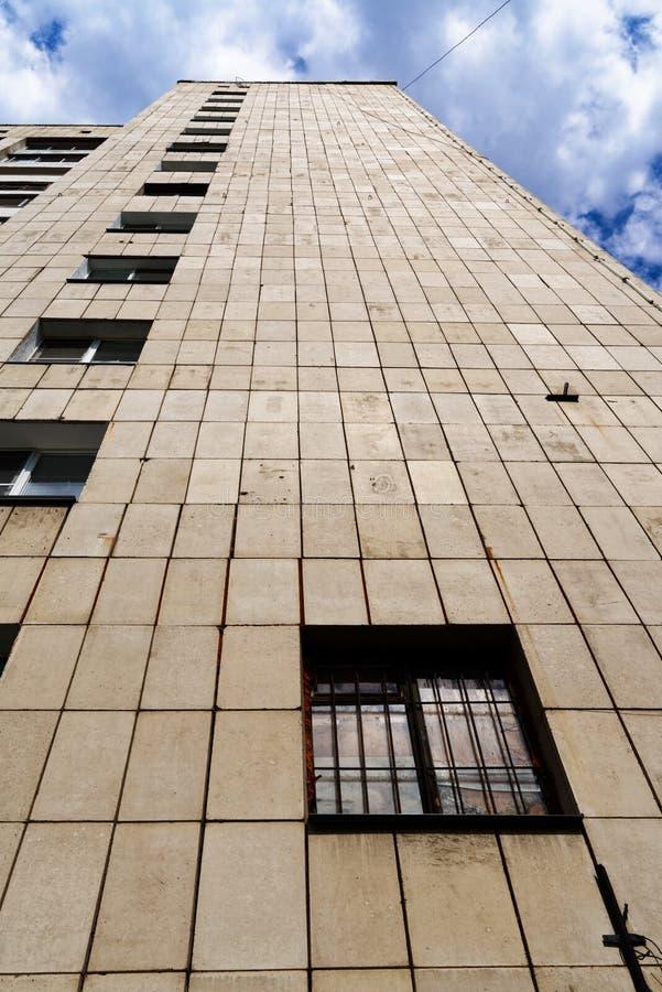 Facciata di vecchio alto aumento contro cielo blu nuvoloso fotografia stock libera da diritti