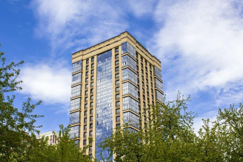 Facciata di vetro di un grattacielo moderno con gli alberi verdi contro un cielo blu con le nuvole bianche fotografia stock