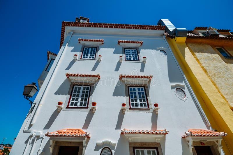Facciata imbiancata della casa con i vasi da fiori marroni in Cascais, Portogallo fotografia stock