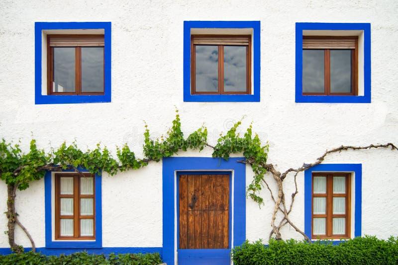 Facciata imbiancata della casa con le finestre blu fotografia stock