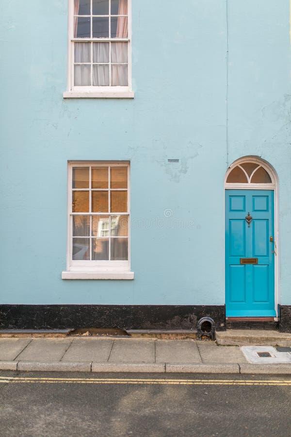 Facciata inglese classica della casa con la porta e finestra osservata dall'aria aperta immagini stock libere da diritti