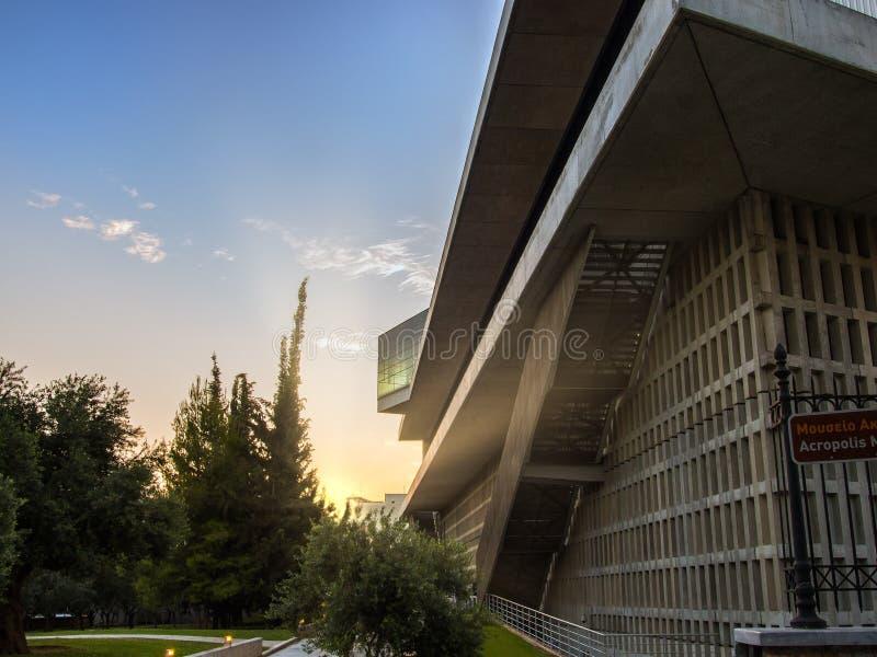 Facciata laterale del museo dell'acropoli Atene, in Grecia e giardino accanto contro il tramonto immagine stock libera da diritti