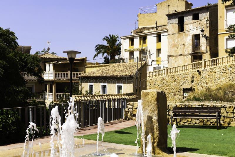 Facciate delle case con i tetti piastrellati di vecchia città spagnola e di un cortile accogliente con una fontana, costruiti nel immagine stock