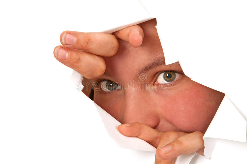 Face. Young woman looking through a hole of a paper wall royalty free stock photography