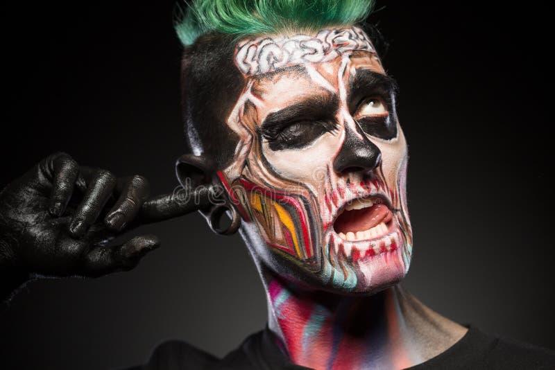 Face art concept, briht skull makeup on mans face. royalty free stock image