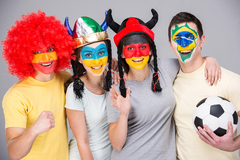Face art. Flags. International team. Four smiling young fans with national flags painted on the faces stock image