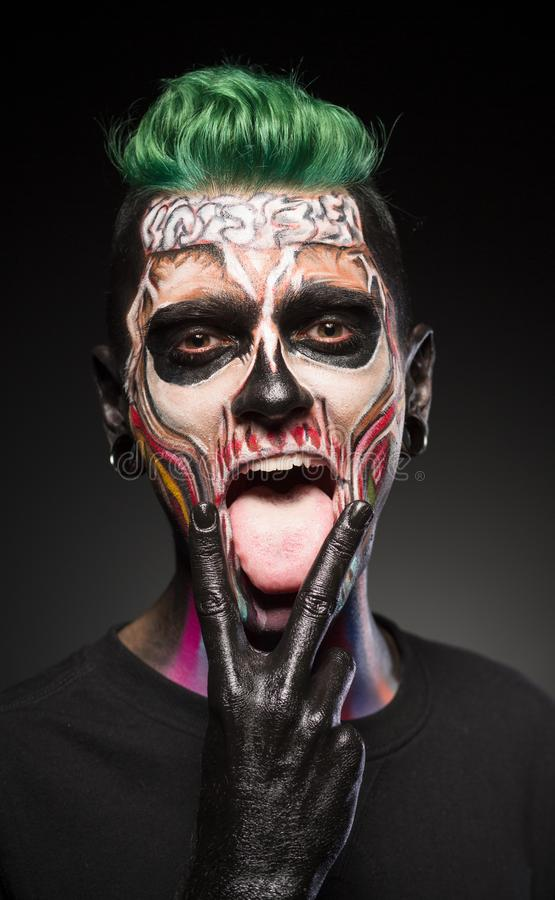 Face art, man with green hair and bright skull makeup showing tongue. stock photo