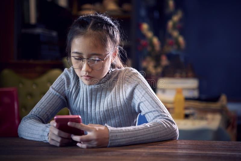 Face of asian teenager reading message on smart phone in home li stock photos