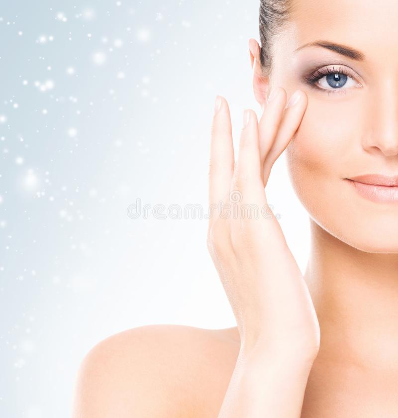 Face of attractive and healthy woman over seasonal Christmas background with a winter snowflakes. Healthcare, spa, makeup and face stock image