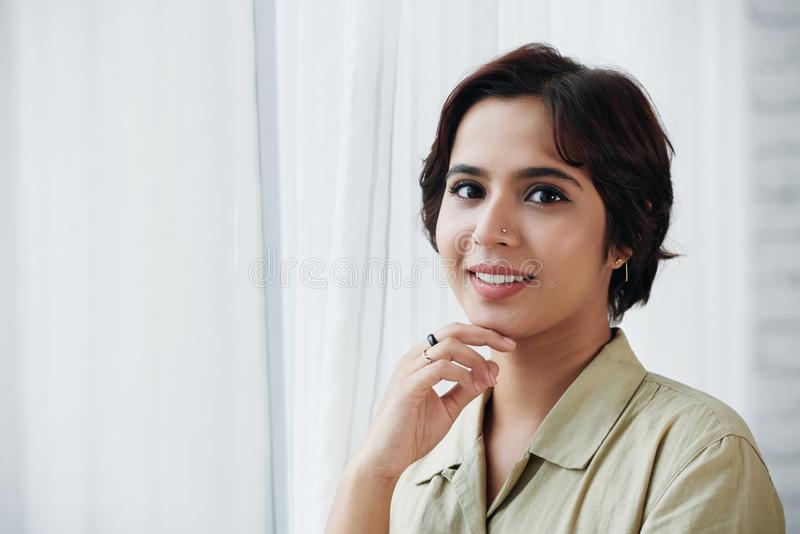 Beautiful Indian woman. Face of attractive young Indian woman standing at window and looking at camera royalty free stock photo
