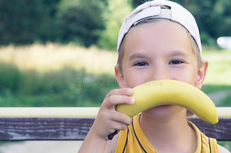 Face of a beautiful young caucasian boy with banana mustache on nature background. royalty free stock photo