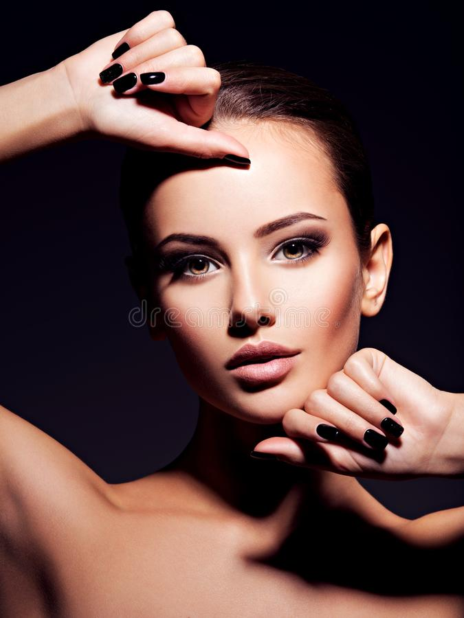 Face of a beautiful girl with fashion makeup and black nails. Posing at studio over dark background royalty free stock image