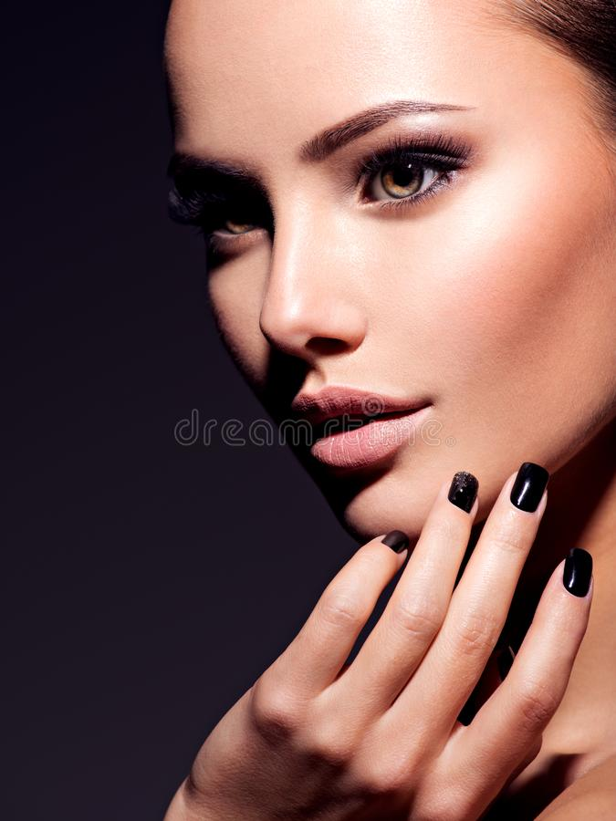 Face of a beautiful girl with fashion makeup and black nails. Posing at studio over dark background royalty free stock photos