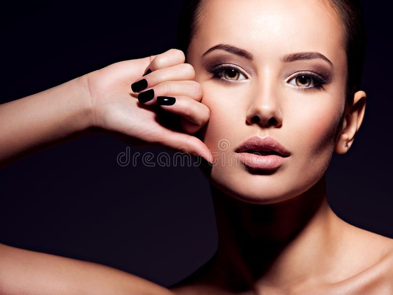 Face of a beautiful girl with fashion makeup and black nails. Posing at studio over dark background royalty free stock photography