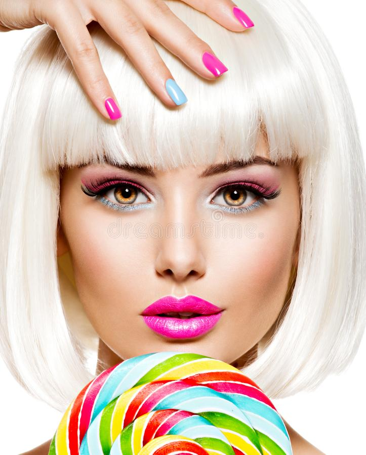 Face of a beautiful  girl with pink eye make-up and multicolor nails. Sweet candy. Close-up face of a beautiful  girl with brown eye makeup and bright multicolor royalty free stock photos