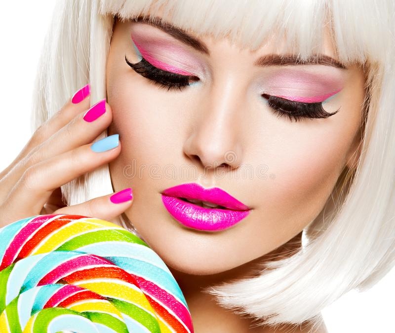 Face of a beautiful  girl with pink eye make-up and multicolor nails. Sweet candy. Close-up face of a beautiful  girl with brown eye makeup and bright multicolor stock image