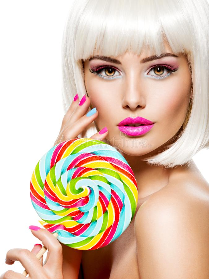 Face of a beautiful  girl with pink eye make-up and multicolor nails. Sweet candy. Close-up face of a beautiful  girl with brown eye makeup and bright multicolor stock images