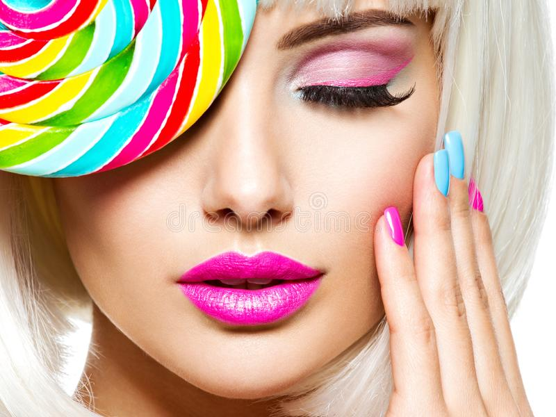 Face of a beautiful  girl with pink eye make-up and multicolor nails. Sweet candy. Close-up face of a beautiful  girl with brown eye makeup and bright multicolor royalty free stock photo