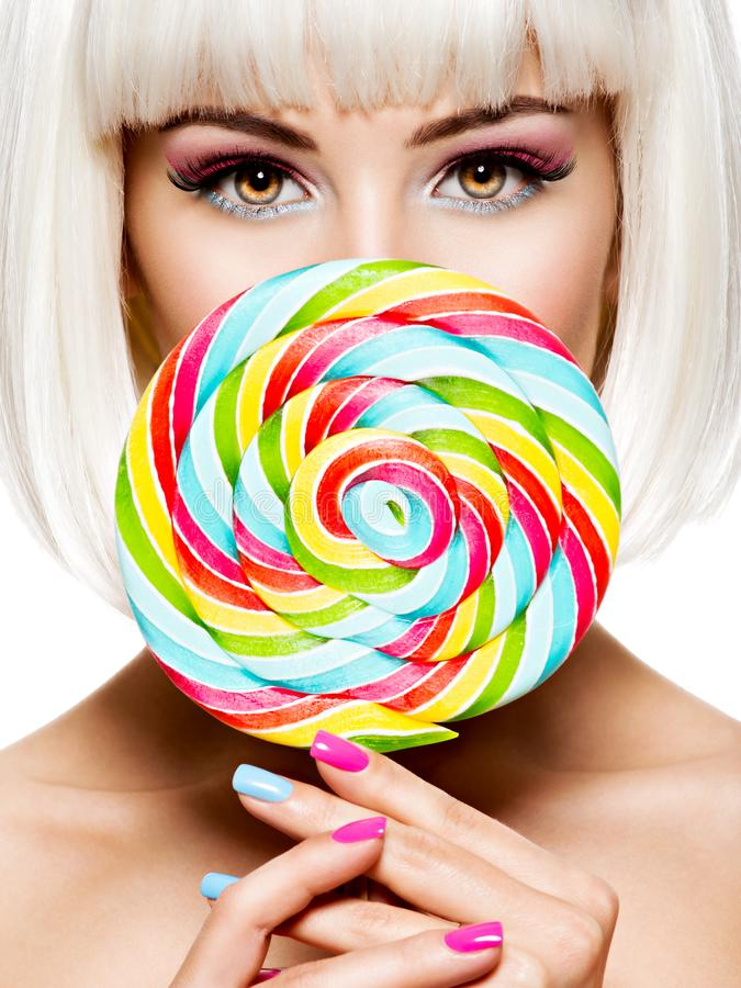 Face of a beautiful   girl with pink eye make-up and sweet candy. Face of a beautiful  girl with pink eye make-up and multicolor sweet candy. Fashion model stock photo
