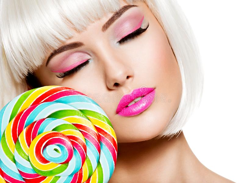 Face of a beautiful  girl with pink make-up and multicolor sweet candy. Face of a beautiful  girl with pink eye make-up and multicolor sweet candy. Fashion model royalty free stock images