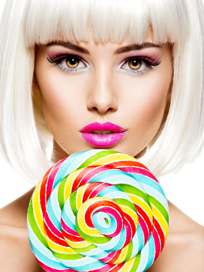 Face of a beautiful  girl with pink make-up and multicolor sweet candy. Face of a beautiful  girl with pink eye make-up and multicolor sweet candy. Fashion model royalty free stock image