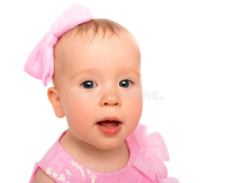 Face of a beautiful little baby girl with a pink bow isolated royalty free stock image