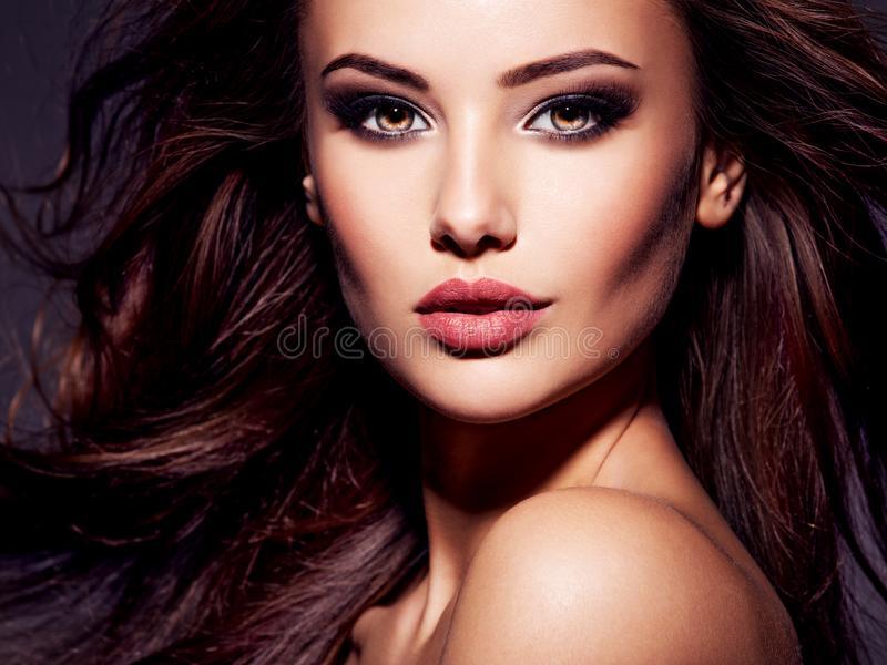 Face of the beautiful sexy woman with long brown hair. Face of the beautiful woman with long brown curly hair posing at studio over dark background royalty free stock photo
