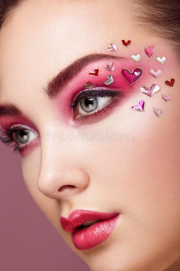 Face of beautiful woman with holiday makeup heart. Valentine`s Day Make-up. Lips in Pink Lipstick. Makeup detail. Face of Girl on a Pink Background royalty free stock image