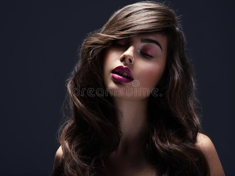 Face of a beautiful woman with long brown curly hair. Fashion model with wavy hairstyle. Attractive young  girl with curly hair. Posing at studio. Female face stock photography