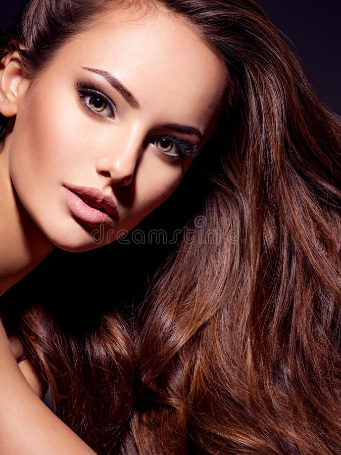 Face of the beautiful sexy woman with long brown hair. Face of the beautiful woman with long brown curly hair posing at studio over dark background stock images