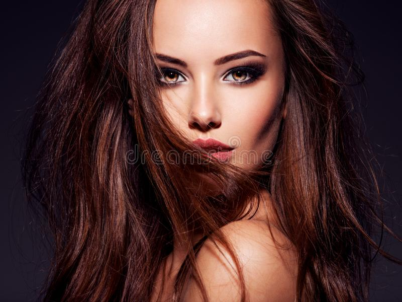Face of the beautiful sexy woman with long brown hair. Face of the beautiful woman with long brown curly hair posing at studio over dark background stock photos