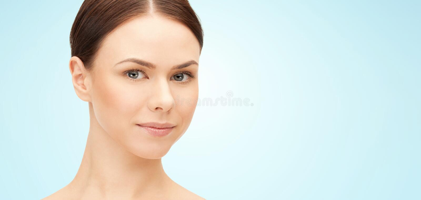 Face of beautiful woman over blue background royalty free stock photography
