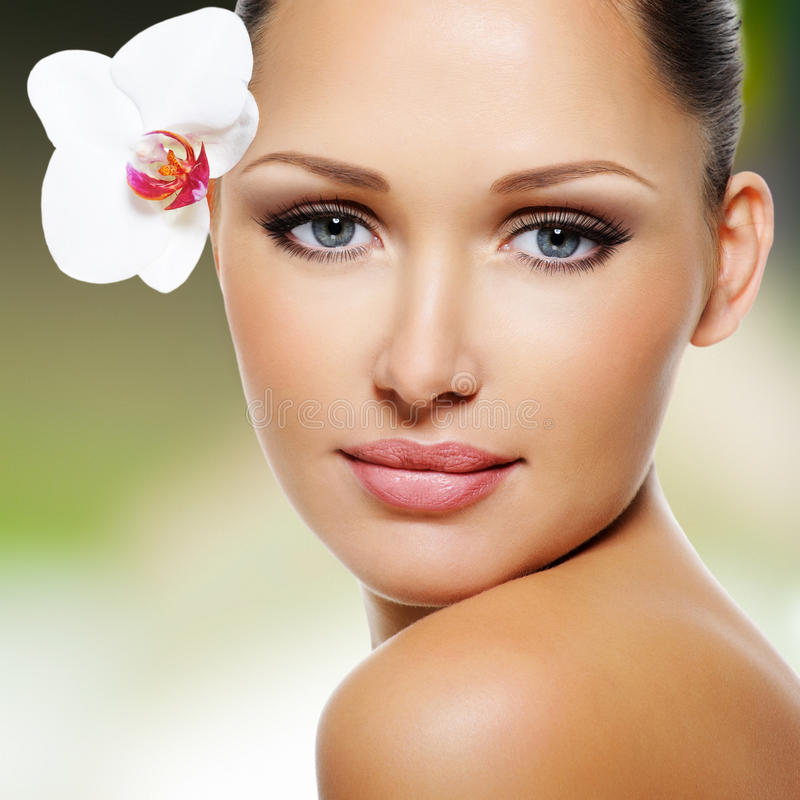 Face of beautiful woman with a white orchid flower royalty free stock photos