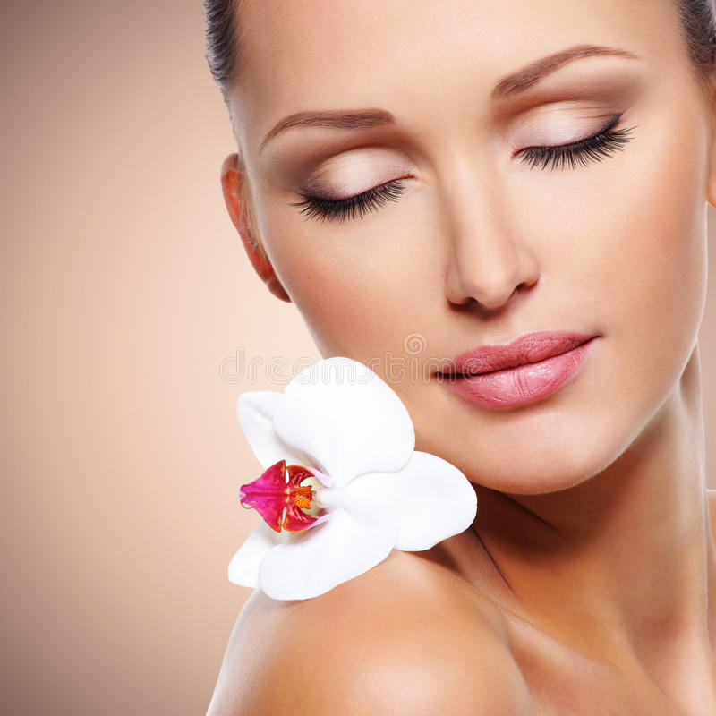 Face of beautiful woman with a white orchid flower stock photos