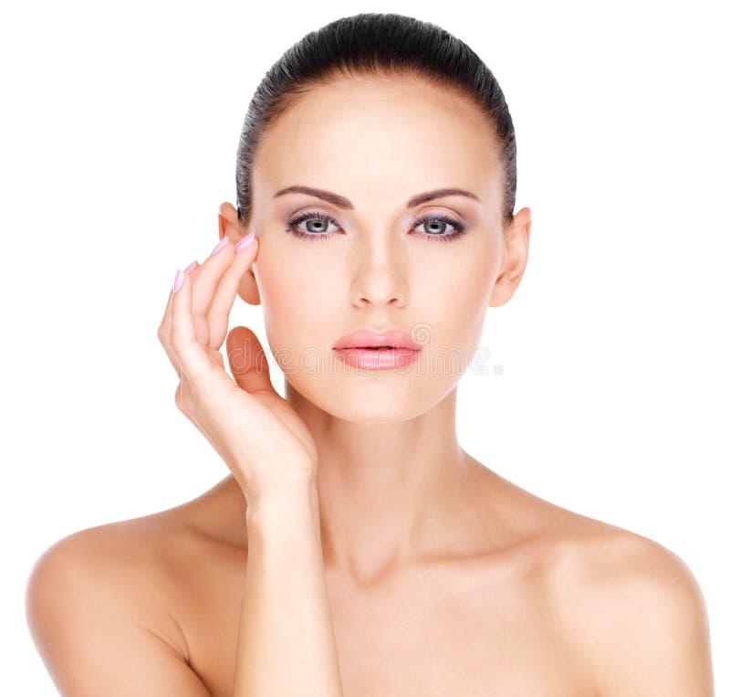 Face of a beautiful woman who touching skin near eyes stock image