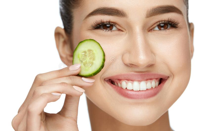 Face Beauty Care. Beautiful Woman With Natural Makeup. Removing Dark Circles With Slice Of Cucumber. High Resolution stock images