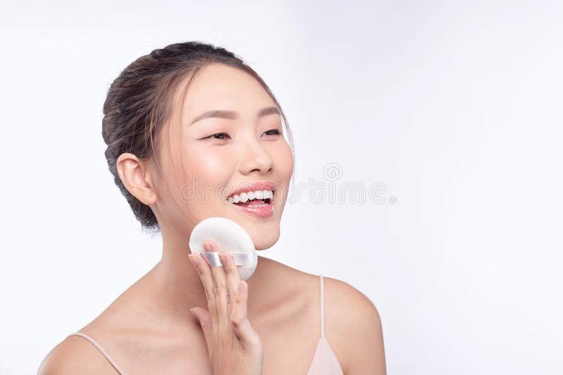Face of beauty young woman applying sponge - isolated on white.  royalty free stock image