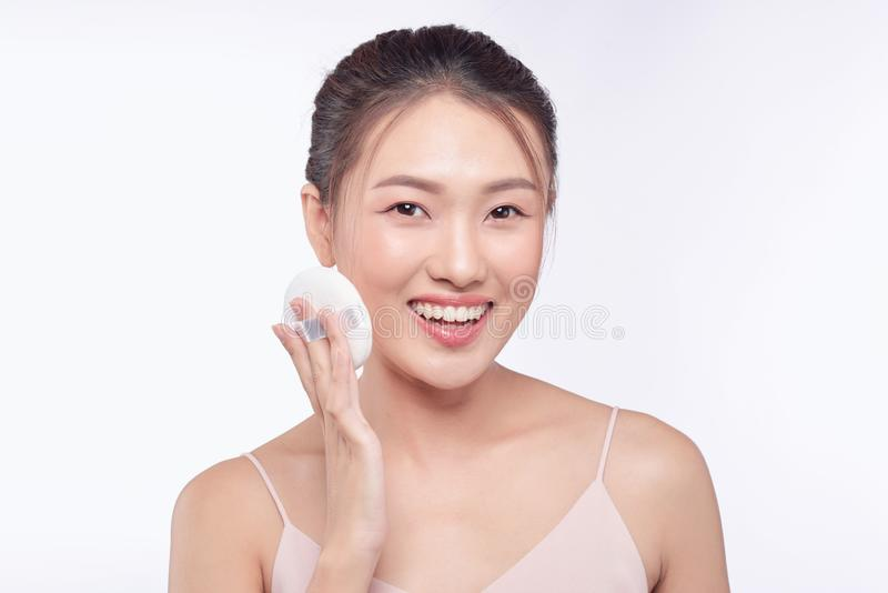 Face of beauty young woman applying sponge -  on white.  royalty free stock image