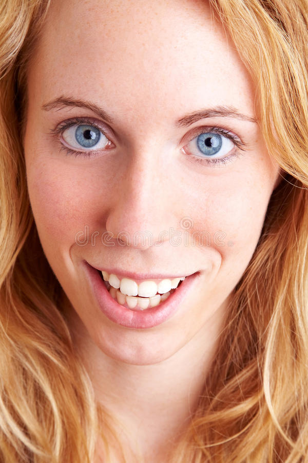 Face of a blonde. Young blond woman smiling into the camera royalty free stock photo