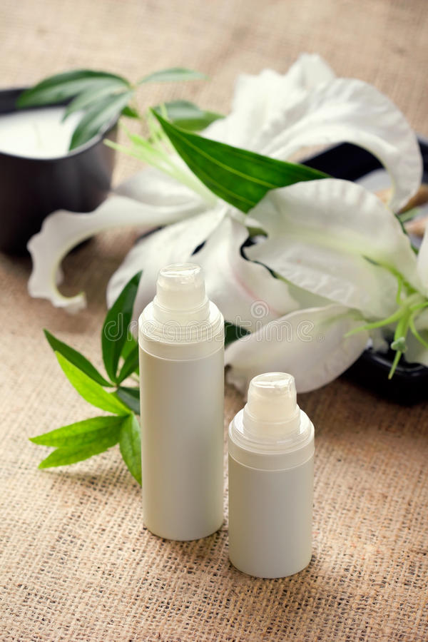 Face/body care concept: lily flower with creams. Face/body care concept: bottles of creams/lotions/serums with white lily flowers, closeup shot royalty free stock photos